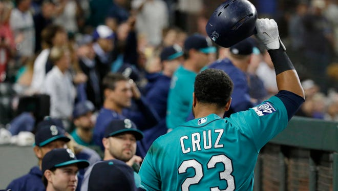 Nelson Cruz salutes the Safeco Field crowd on Friday after hitting the 300th home run of his major league career. Cruz has hit 103 of those homers since joining the Mariners 2 1/2 years ago.