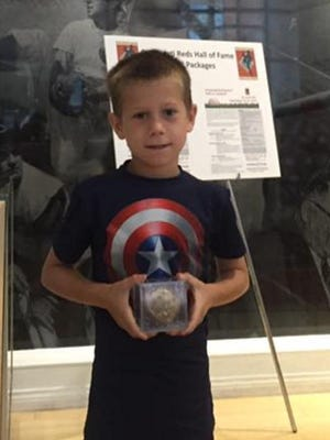 Lance, son of Wade Yuellig, holds a baseball signed by Babe Ruth, Ted Kluszewski, Hank Aaron and Pete Rose. The ball also saw its share of action by at least two generations of Yuelligs. It's now on loan to the Cincinnati Reds Hall of Fame Museum.