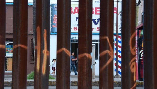 A woman and child walk past a barbershop in Nogales, in the Mexican state of Sonora, as seen Oct. 12, 2016, through the border fence in Nogales, Ariz.