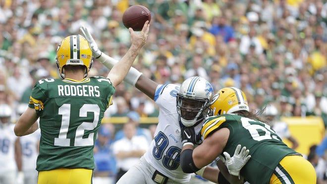 Green Bay Packers quarterback Aaron Rodgers (12) throws under pressure as tackle David Bakhtiari (69) blocks against the Detroit Lions defensive tackle Khyri Thornton (99) at Lambeau Field  September 25, 2016.