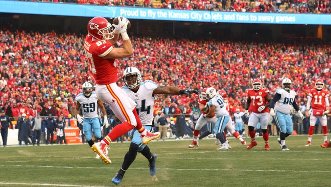 Kansas City Chiefs tight end Travis Kelce (87) catches a touchdown pass over Tennessee Titans inside linebacker Avery Williamson (54) during the first quarter in the AFC wild-card playoff game at Arrowhead Stadium.
