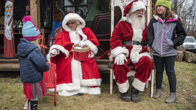 Emma Woods, 3, left,and Rylee Day, 9, right, meet Santa and Mrs. Claus on Saturday, Dec. 5, 2020, at Loveberry's Tree Farm in Quincy, Mich.