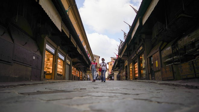 People walk across the Ponte vecchio bridge, in Florence, Wednesday, June 3, 2020. The Uffizi museum reopened to the public after over two months of closure due to coronavirus restrictions.