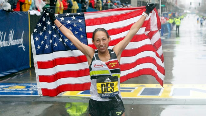 Former ASU standout Desiree Linden of the U.S. holds up the American flag after winning the Women's Division of the 2018 Boston Marathon on April 16, 2018.