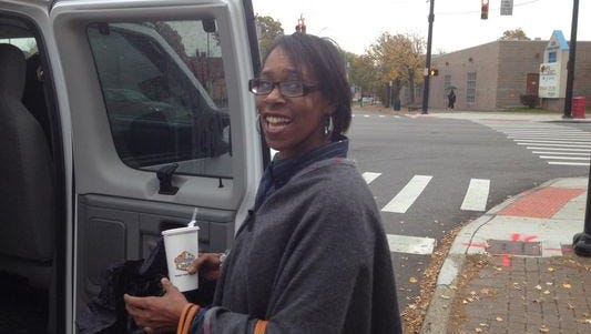 """Sheroin Evans, 45, of Avondale, boards a church van at the corner of Reading Road and Forest Avenue on Friday to vote Downtown at the Hamilton County Board of Elections. Several civil rights groups, nonprofit social agencies and black churches coordinated """"Get Out the Vote"""" events for early voting period, including busing voters to the Hamilton County Board of Elections."""