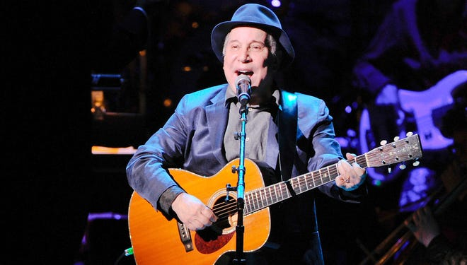 """Paul Simon perform the song """"Bridge Over Troubled Water"""" at the 25th Anniversary Rainforest Fund benefit concert at Carnegie Hall on Thursday, April 17, 2014 in New York. (Photo by Evan Agostini/Invision/AP)"""