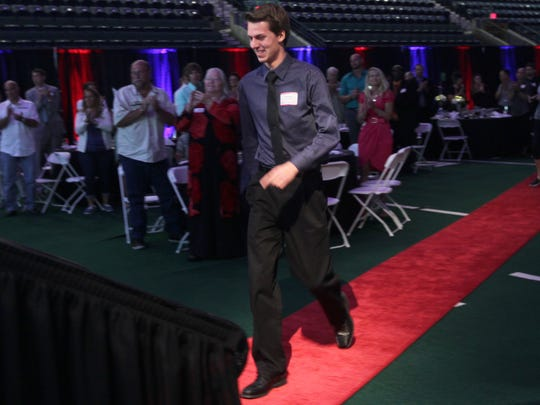 Male Athlete of the Year winner Josh Kennedy walks up onto the stage to get his trophy Tuesday at the All-Area Stars Awards Banquet in Fort Myers.