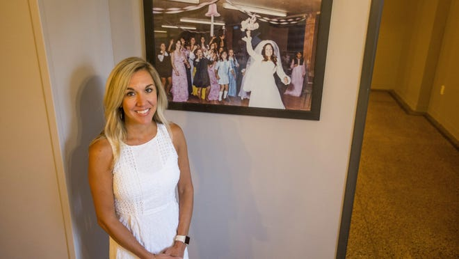 Melanie Kennedy stands next to a wedding photo of her mother in the old Niles Elks Lodge building.