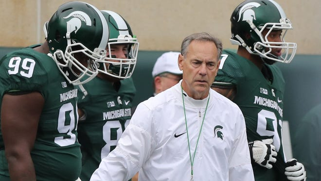 Michigan State Spartans head coach Mark Dantonio shakes hands with his players Saturday, Oct. 29, 2016 at Spartan Stadium before the game against the Michigan Wolverines in East Lansing.