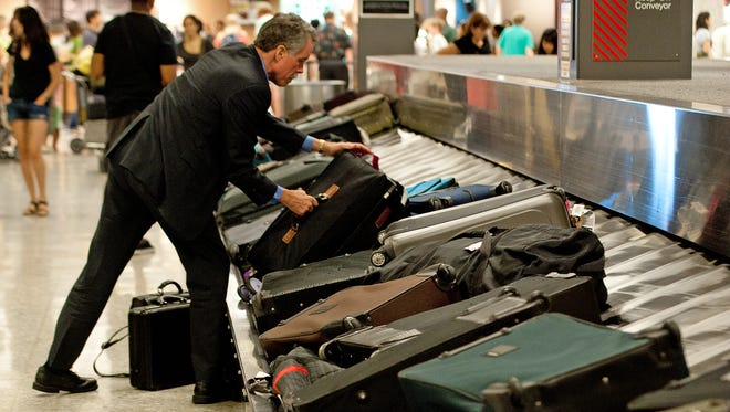A traveler reaches for his luggage inside Dulles International Airport near Washington, DC.