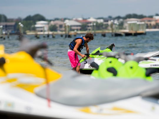 Radical Rides employee Blaine Gavin prepares a personal watercraft for Pensacola Beach visitors in September 2016.