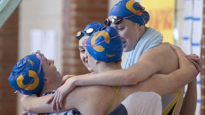 Sammie Burchill, Emma Nordin, Trude Rothrock and Amy Bilquist celebrate winning the 400 yard freestyle relay during the Metropolitan Interscholastic Conference swimming and diving championships at Carmel High School's Eric Clark Activities Center, Saturday, Jan. 10, 2015.