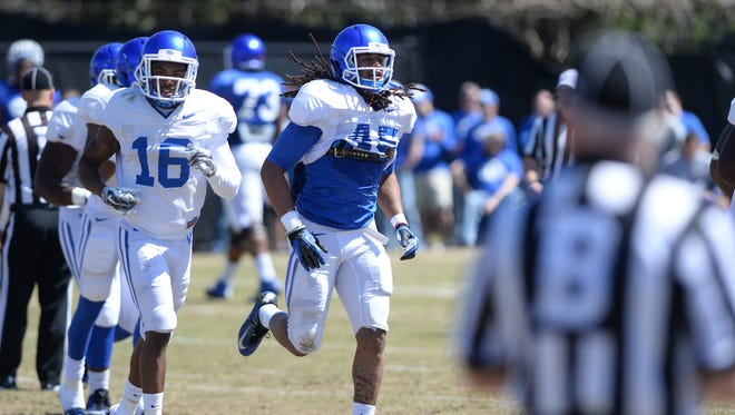 Senior LB Josh Forrest runs off the field after making an interception during the Kentucky football scrimmage on Saturday, April 11, 2015.