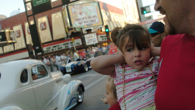Alexee Proffitt, 3, covers her ears as passing drivers rev their engines during the Hot August Nights cruise and fireworks show on Virgina Street on Friday night in Reno.