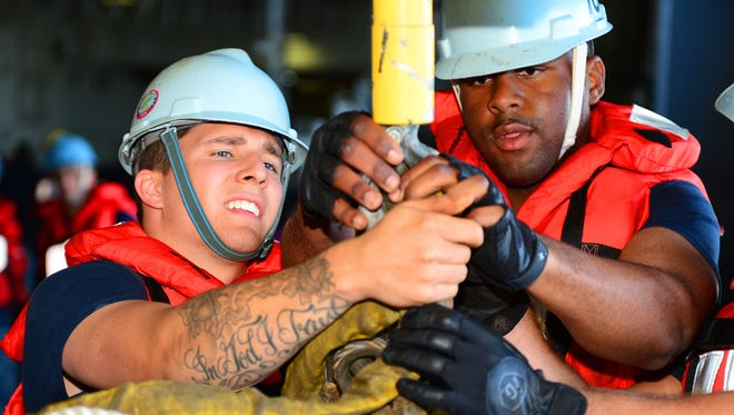 New rules allow sailors to have tattoos on their necks, hands, forearms and more, as part of changes meant to recruit and retain from a generation where more than 1 in 3 have tattoos. Here, Boatswain's Mate Seaman Luke Liggett, left, and Seaman Yoshemi Walters rig a hook during a replenishment-at-sea on the aircraft carrier Ronald Reagan.