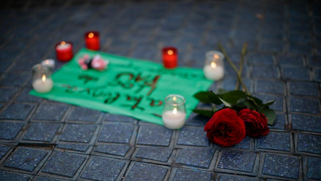 Flowers and candles are placed on the pavement on a street in Las Ramblas, Barcelona, Spain, Friday, Aug. 18, 2017. Spanish police on Friday shot and killed five people carrying bomb belts who were connected to the Barcelona van attack that killed at least 13, as the manhunt intensified for the perpetrators of Europe's latest rampage claimed by the Islamic State group. (AP Photo/Manu Fernandez)