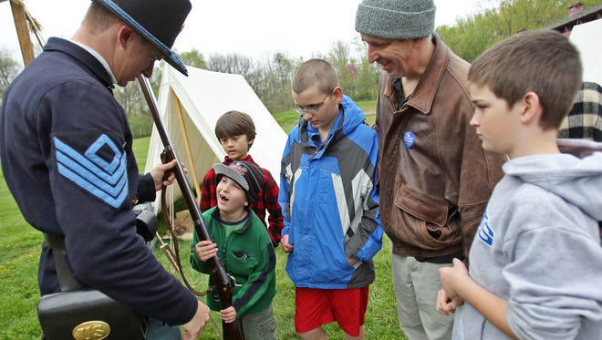 Brandon Kreisher, left, acting as a first sergeant in the Union army during the Civil War, shows Conner Prairie visitors, including, from left, Benjamin Harris, 7, in green, Andrew Atkinson, 10, Matthew Harris, 13, Andy Harris, and Jacob Harris, 10, how heavy his 9lb 1861 Springfield rifled musket is, during opening weekend, Saturday, March 31, 2012.  The family and their friend participated in the opening weekend's Amazing Race Through Time, by learning and testing their skills on a menu of activities around the interactive museum.  At this point, they were to report to the officer in command and get their orders.  Kelly Wilkinson / The Star
