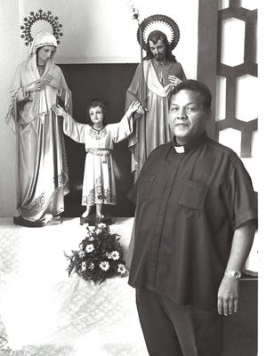 Asan village priest, Father Ray Techaira stands next to the Holy Family, Joseph, Mary and Jesus, in the Nino Perdido Church in Asan. on May 28, 1989.