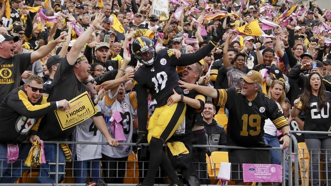 Pittsburgh Steelers wide receiver JuJu Smith-Schuster (19) celebrates with fans after scoring a touchdown in the first half of an NFL football game against the Baltimore Ravens, Sunday, Oct. 6, 2019, in Pittsburgh. With the COVID-19 pandemic, professional and college sports currently remain subject to Pennsylvania's state-ordered limit of fewer than 250 people on site for games and practices.