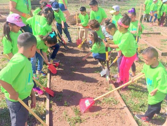Students rake the garden area.