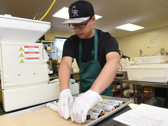 Chinese graduate student Runjia Wang rolls sushi at Colorado State University on Sept. 28. The university recently bought a sushi robot that can produce up to 300 rolls per hour.