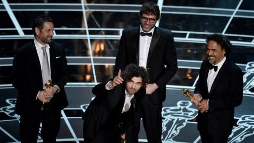 """Alexander Dinelaris, from left, Armando Bo, Nicolas Giacobone, and Alejandro G. Inarritu accept the award for the best original screenplay for """"Birdman or (The Unexpected Virtue of Ignorance)"""" at the Oscars on Sunday, Feb. 22, 2015, at the Dolby Theatre in Los Angeles. (Photo by John Shearer/Invision/AP)"""