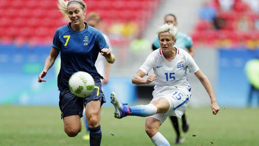 """In this Friday, Aug. 12, 2016, file photo, United States' Megan Rapinoe, right, kicks the ball past Sweden's Lisa Dahlkvist during a quarterfinal match of the women's Olympic soccer tournament in Brasilia. Rapinoe knelt during the national anthem Sunday, Sept. 4, before the Seattle Reign's game against the Chicago Red Stars """"in a little nod"""" to NFL quarterback Colin Kaepernick. (AP Photo/Eraldo Peres, File)"""