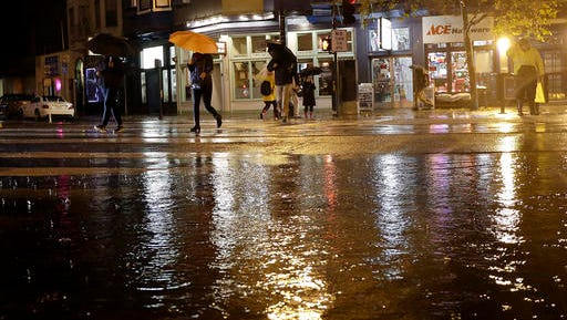 FILE - In this Dec. 15, 2016, file photo, pedestrians walk past a puddle at a flooded intersection in San Francisco. California's first winter storm of 2017 will shed welcome rain over the rivers, pumps and pipes that move California's water from north to south, and may open a new era of tensions over where that water goes, under a new federal law dictating that the state's farmers get the biggest possible share.