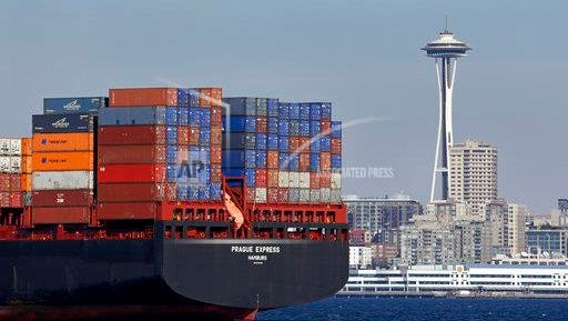 FILE - In this Feb. 15, 2015, file photo, the Space Needle towers in the background beyond a container ship anchored in Elliott Bay near downtown Seattle. U.S. employers are thought to have hired at a brisk pace in February, and the unemployment rate is expected to stay low _ a result that would provide further evidence of a consistently solid job market.