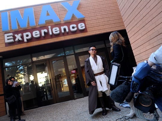 "Russel Rosales of California speaks with a television reporter Thursday in front of the Fort Worth Museum of Science and History's IMAX theater. Rosales was there to see the early screening of ""Star Wars: The Last Jedi"" and was himself dressed as a Jedi."
