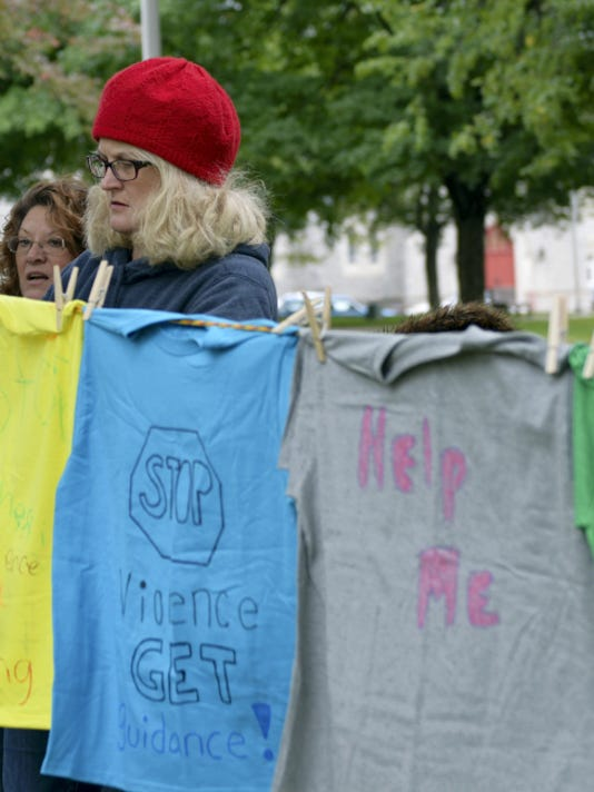 Blair Beard of Domestic Violence Intervention of Lebanon County hangs a tee shirt on the line for The Clothesline Project held on Sunday at Monument Park. Barbara West-Lebanon Daily News