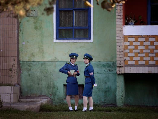 North Korean traffic police women chat next to a residential