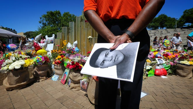 Michael Johnson looks for a place to put a photo of Muhammad Ali at the makeshift memorial at the Muhammad Ali Center on Monday.June 6, 2016