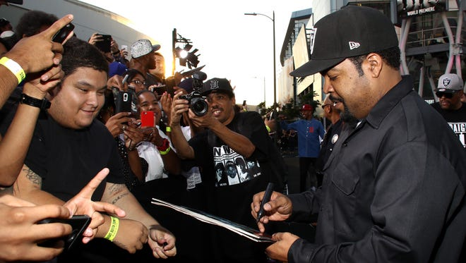"""Ice Cube signs an autographs as he arrives at the Los Angeles premiere of """"Straight Outta Compton"""" at the Microsoft Theater on Monday, Aug. 10, 2015."""