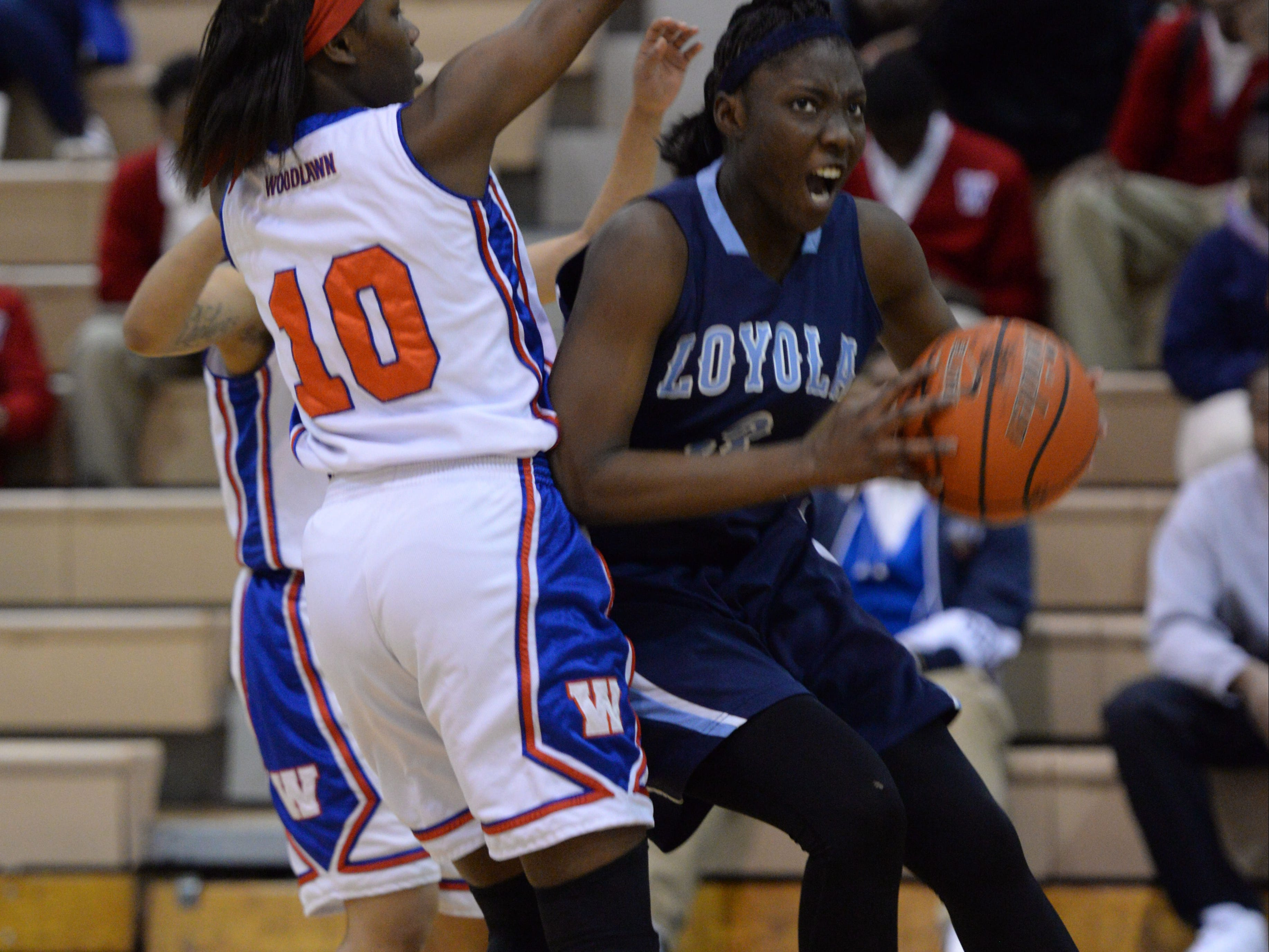 Amber Smith of Loyola drives past Woodlawn's Aliyah Carter during Friday night's game.