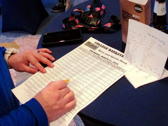 A gambler looks over a race and sports book sheet for the NCAA basketball tournament Thursday, March 21, 2019, at the Borgata casino in Atlantic City N.J. This is the first March Madness tournament since legal gambling expanded last year following a U.S. Supreme Court ruling involving a case brought by New Jersey. (AP Photo/Wayne Parry)
