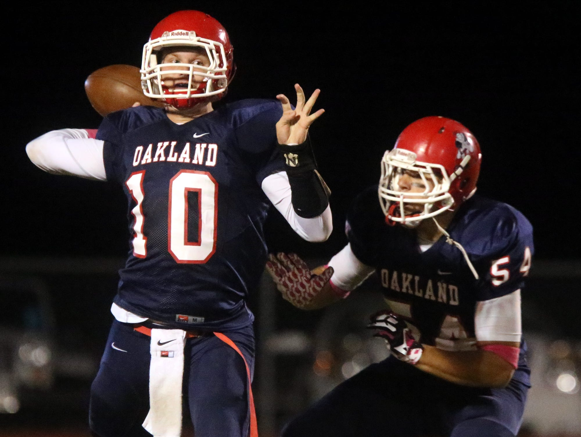 Oakland's quarterback Brendan Matthews (10) drops back to pass the ball as his teammate Jacob Frazier (54) guards Matthews during the game against Riverdale at Oakland, on Friday Oct. 16, 2015.