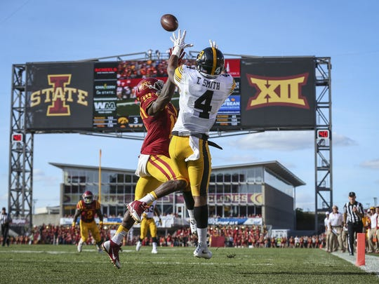 Iowa's (4) Tevaun Smith (4) pulls in a touchdown pass in front of Iowa State's (10) Brian Peavy during the first half of their football game Saturday, Sept. 12, 2015, at Jack Trice Stadium in Ames, Iowa.