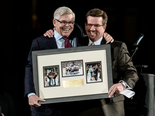 Dave Andrews, left, president and CEO of the American Hockey League, presents Doug Yingst with a gift as the Hershey Bears honored Yingst on Saturday night.