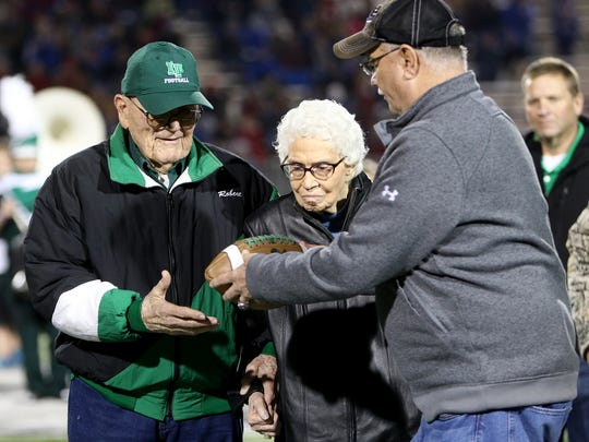 Former Iowa Park coach Weldon Nelms gives Robert Wilcox a signed football for his 70 years of service as Iowa Park's stadium announcer.