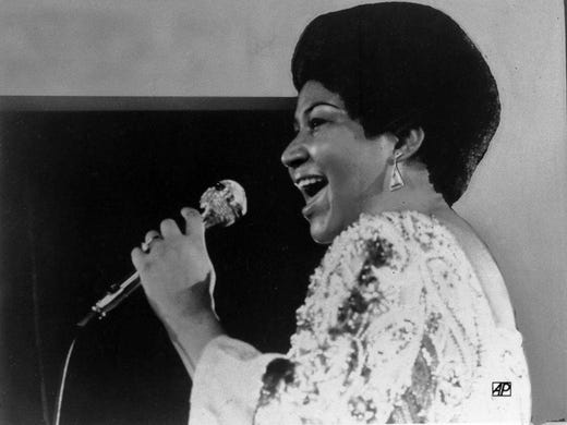 Vocalist Aretha Franklin warbles a few notes into microphone