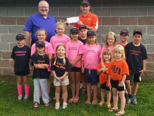 Dave Stager, left, Pro-Am Committee member, and Dave Kemp, Knoxville Youth Baseball/Softball Association League president, with league players.