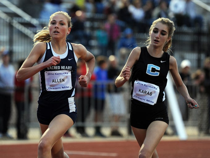 Maggie Allen (left) of Sacred Heart and Gabriella Karas (right) of Collins High School lead the pack in the 2014 Kentucky Dream Mile on Friday at St. Xavier High School. Allen won the event with a time of 4:59.99. Karas placed second with a time of 5:04.43. May 2, 2014