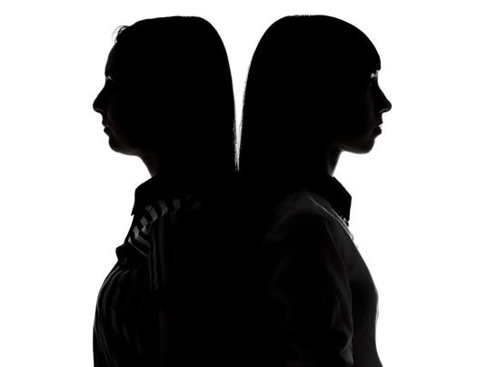 Silhouette of women standing back-to-back