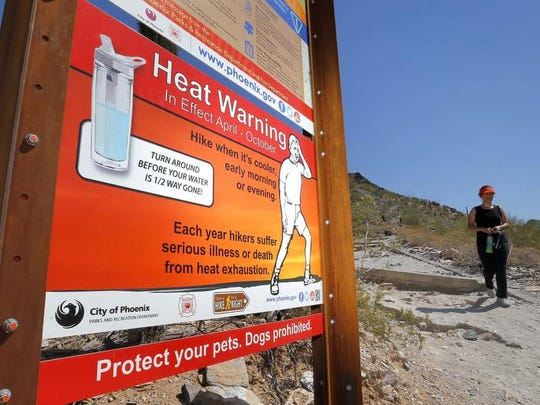 Signs waring of extreme heat are placed on a trailhead,