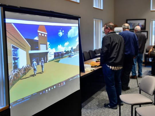 A three-dimensional, moving mockup of the proposed Sartell community center project plays in the foreground as Sartell residents and other interested parties look over plans for the project Tuesday.