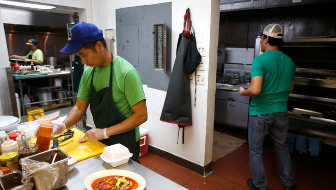 Eric Egina, part owner of Real Sarap, works in the kitchen with his ownership partners at their restaurant on Tuesday, July 7, 2015.