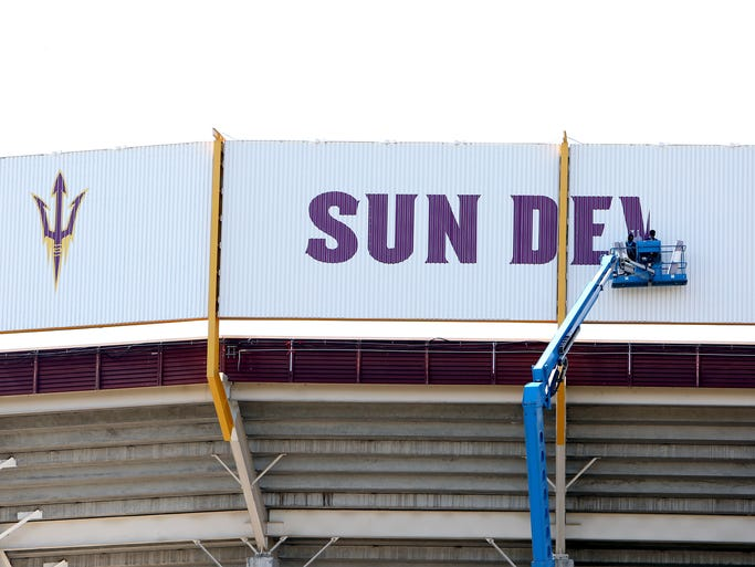 Painters at Arizona State University finish off the Sun Devil name on the North end zone of Sun Devil Stadium. Over the last six months the stadium has opened up the stadium on that side as seen August 26, 2014