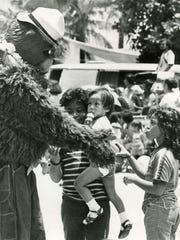 Pacific Daily News file photoSmokey the Bear and timid spectators shaking hands at the 1979 Liberation parade.
