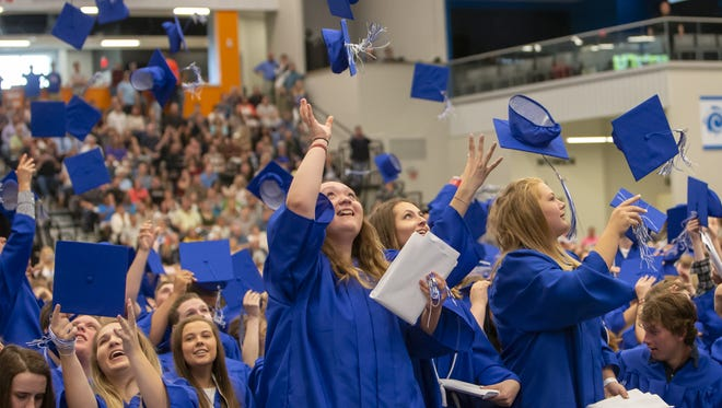 Graduates of Oshkosh West High School toss their caps during the commencement ceremony at Menominee Nation Arena on June 3, 2018.